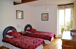 La chambre avec les lits jumeaux et vue sur le jardin